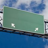 Blank freeway sign in blue cloudy sky. Customizable green blank freeway sign with arrows royalty free stock photo
