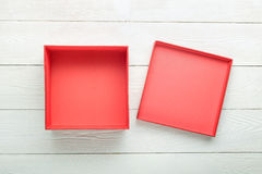Blank gift box with lid. Blank red gift box with lid on white wooden background. Flat lay. View from above Royalty Free Stock Photography
