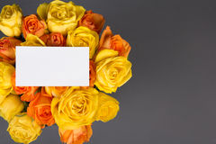 Blank gift card and beautiful bouquet of orange and yellow roses Stock Image