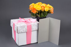 Blank gift card, bouquet of rose flowers and gift box over grey Stock Image