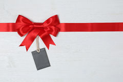 Blank gift tag with bow for gifts on a wooden background Royalty Free Stock Images