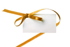 Blank gift. Tag tied with a bow of gold satin ribbon. Isolated on white, with soft shadow Stock Photo