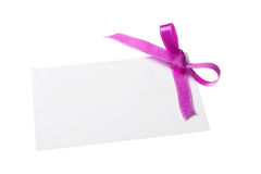 Blank gift tag tied with a bow of purple satin ribbon. Isolated on white, with soft shadow Royalty Free Stock Photography