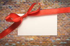 Blank gift tag tied. With a bow of red satin ribbon Royalty Free Stock Photos