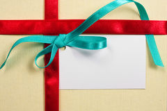 Blank gift. Tag tied with a bow of red satin ribbon Royalty Free Stock Photo