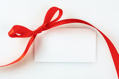 Blank gift tag tied with a bow of red satin ribbon. Close up Royalty Free Stock Image