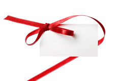 Blank gift tag tied with a bow of red satin ribbon. Isolated on white, with soft shadow Stock Photos