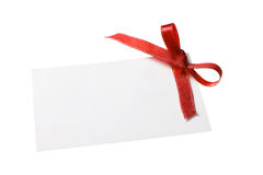 Blank gift tag tied with a bow of red satin ribbon. Isolated on white, with soft shadow. Blank gift tag tied with a bow of red satin ribbon Royalty Free Stock Photos