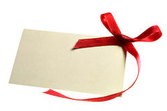 Blank gift. Tag tied with a bow of red satin ribbon. Isolated on white, with soft shadow Stock Image