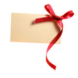 Blank gift tag tied with a bow of red satin ribbon. Isolated on white. With soft shadow Stock Image