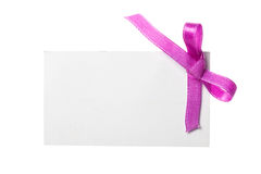 Blank gift tag. Tied with a bow of satin ribbon. Isolated on white, with soft shadow Royalty Free Stock Photography