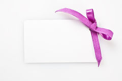 Blank gift tag tied with a bow of satin ribbon. Stock Photos