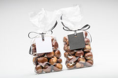 Blank gift tags with ribbon on two chocolate truffles bags Stock Photos