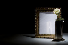 Blank gilded mourning frame with bronze vase, white rose,  and b. Lack tape on dark background Stock Photo