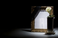 Blank gilded mourning frame with bronze vase, white rose,  and b. Lack tape on dark background Royalty Free Stock Image
