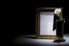 Blank gilded mourning frame with bronze vase, white rose,  and b. Lack tape on dark background Stock Image