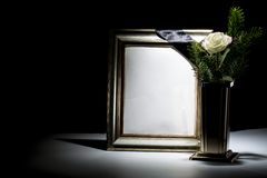 Blank gilded mourning frame with bronze vase, white rose,  and b. Lack tape on dark background Stock Photography