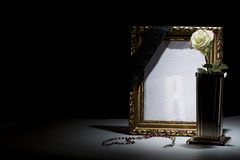 Blank gilded mourning frame with bronze vase, white rose,rosary. Blank gilded mourning frame with bronze vase, white rose, rosary, and black tape on dark Royalty Free Stock Images