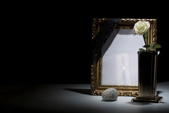 Blank gilded mourning frame with bronze vase, white rose, stone,. And black tape on dark background Royalty Free Stock Photography
