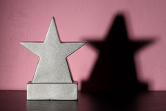 Blank Girl's Trophy. Star shaped trophy and shadow, sitting in a girl's pink bedroom awaiting your engraving royalty free stock photos