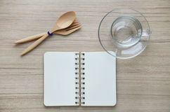 Blank glass and notebook on the wood table - Top view Royalty Free Stock Photos