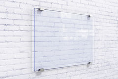 Blank glassy sighnboard on white brick wall Stock Images