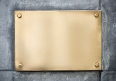 Blank gold or brass metal sign or nameboard on. Wall Stock Photography