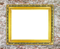 Blank golden frame on ancient stone wall Stock Image