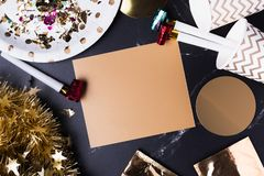 Blank golden greeting card with party cup,party blower,tinsel,confetti.Holiday celebrate party time table top view mock up royalty free stock photography