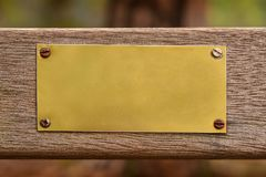 Blank golden metal plate on wood Royalty Free Stock Photo
