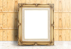 Blank Golden Vintage frame on marble floor and plank wooden wall Royalty Free Stock Photography