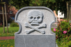 Blank gravestone with skull and crossbones. Blank gravestone decorated with skull and crossbones Stock Photo