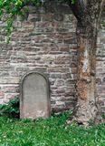Blank gravestone under a tree. Blank gravestone/tombstone under a tree in front of a stone wall. The scene has contrast colors royalty free stock photos