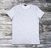 Blank gray t-shirt on a wooden surface stock images