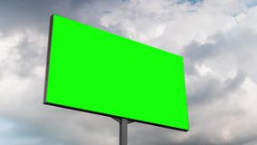 Blank green billboard and moving white clouds against blue sky - timelapse. Green screen, consumerism, time lapse, advertising, template, mock up, copyspace stock video