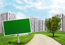 Blank green billboard and tree by road running Stock Images