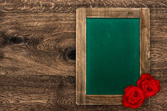 Blank green blackboard with red roses Stock Photography