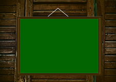 Blank green board on wooden background Royalty Free Stock Photography