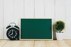 Blank green chalkborad with wood frame and little decorative tre. E in white vase and vintage alarm clock on wooden table with copy space for add text Royalty Free Stock Images