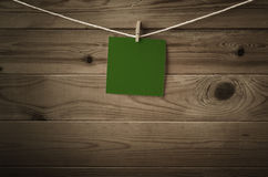 Blank Green Message Pegged to String against Wood Planks. One individual square of festive dark green note paper, pegged to a string washing line with wood plank stock photo