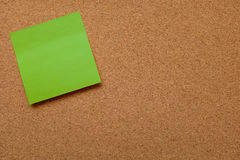 Blank green note paper stuck on cork board. Blank green note paper stuck on cork noticeboard with copy space Stock Photo