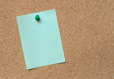Blank green note pinned on cork board Stock Photo