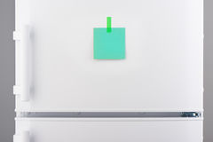 Blank green paper note attached by sticker on white refrigerator Stock Photo