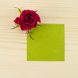 Blank green paper and rose flower on wooden background Stock Photo