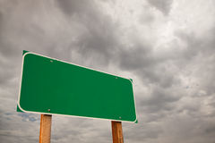 Blank Green Road Sign Over Storm Clouds Stock Photo