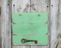 Blank green sign with bronze antique skeleton key hanging on rustic wooden door Stock Image