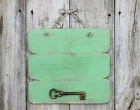 Blank green sign with bronze antique skeleton key hanging on rustic wooden door. Blank green sign with bronze antique skeleton key hanging on weathered wood Stock Image