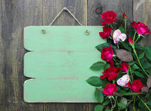 Blank green sign with flowers hanging on wood door Royalty Free Stock Photos