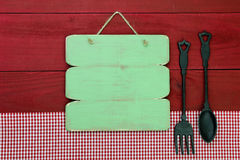 Blank green sign hanging by red gingham tablecloth on wooden background. Blank rustic menu sign by cast iron spoon and fork and red checkered napkin hanging on Royalty Free Stock Photography