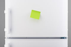 Blank green sticky paper note on white refrigerator Royalty Free Stock Photos